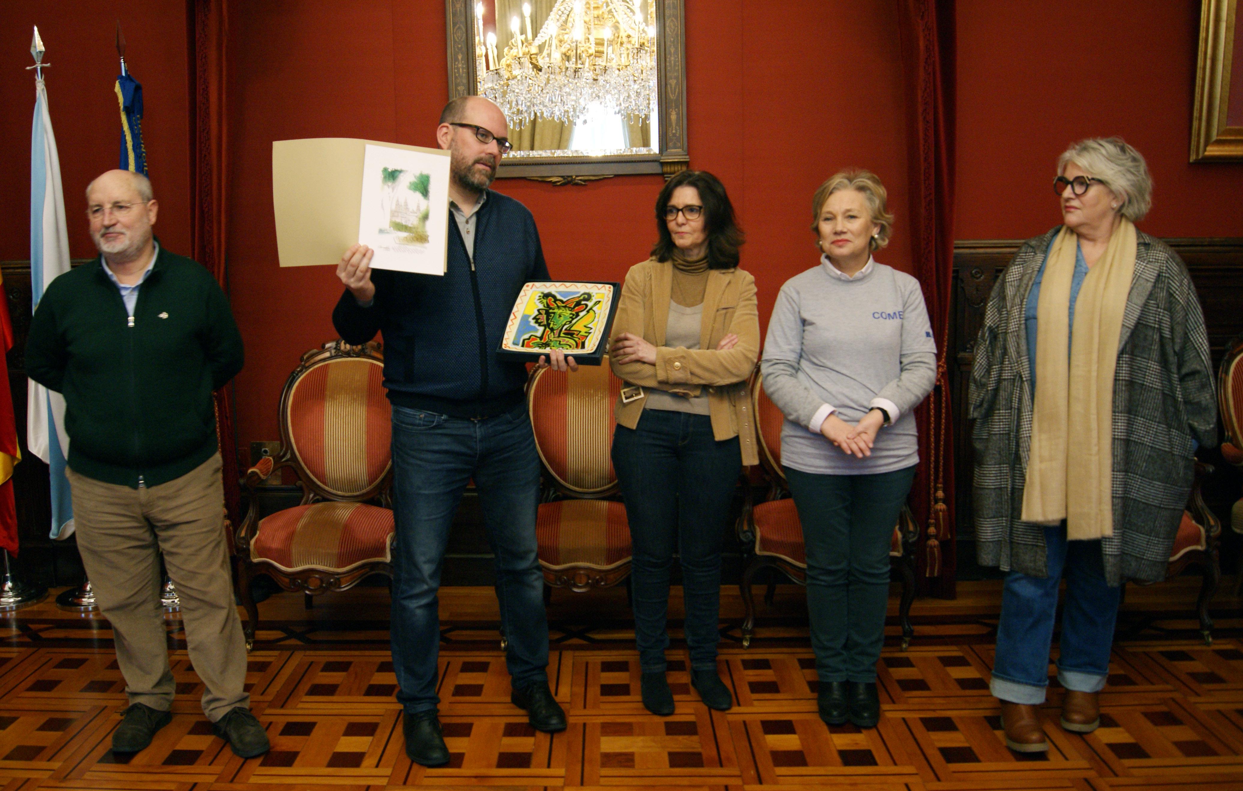 Martiño Noriega amosa os agasallos para os colexios en lembranza do seu paso por Santiago de Compostela.