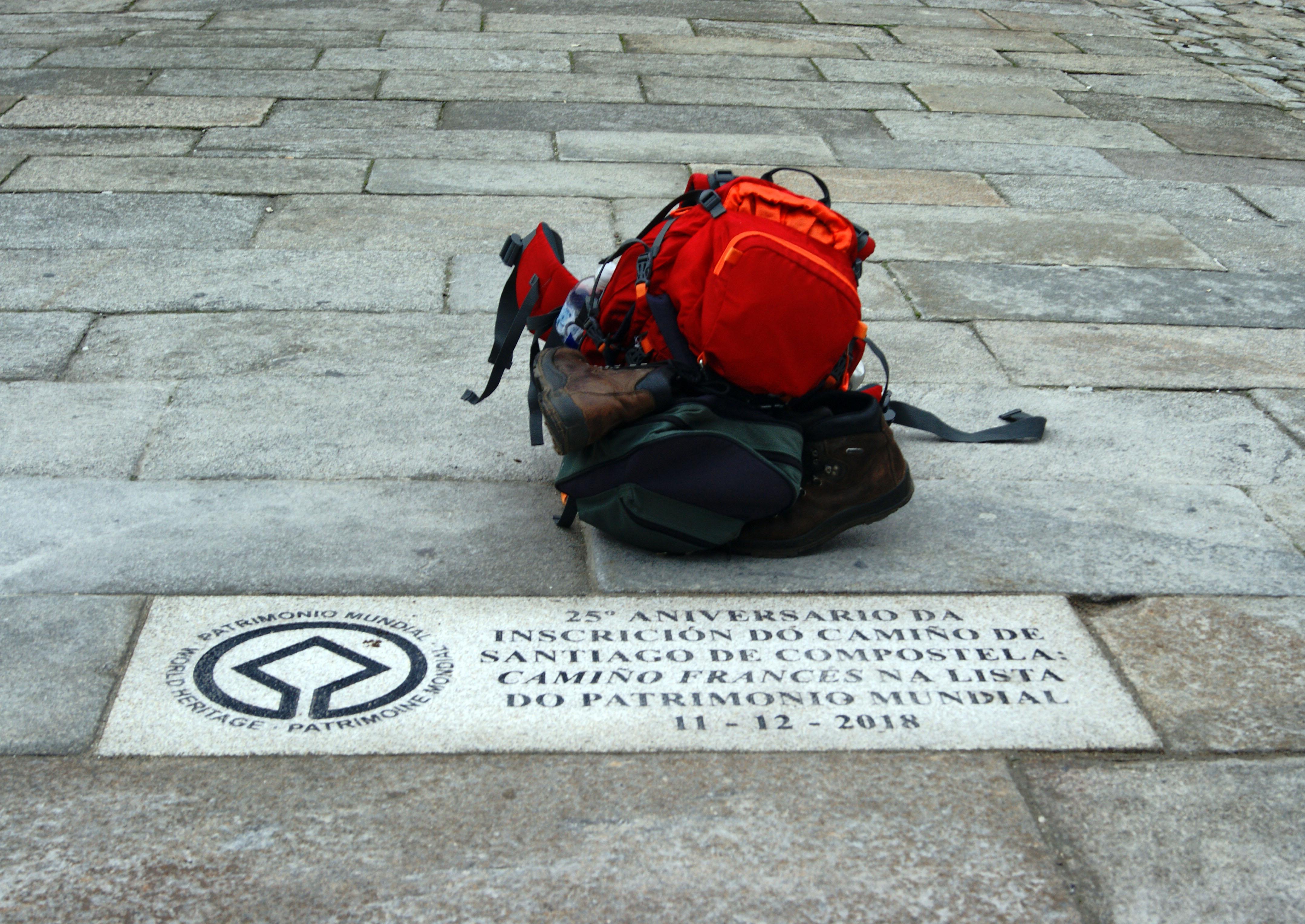 A mochila dun peregrino diante da lousa coa inscrición.
